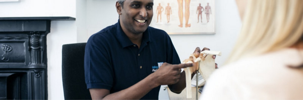 Wide shot of Karthik holding a type of human bone model whilst smiling at a patient.